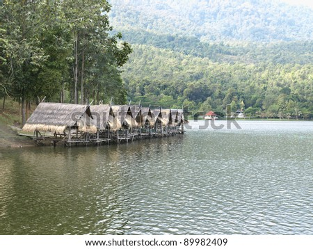 Thatched roof restaurants around the lake, Thailand - stock photo