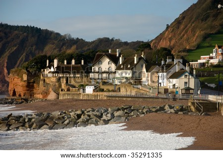 Thatched roofed houses beside the  beach and sea wall in Sidmouth, England - stock photo