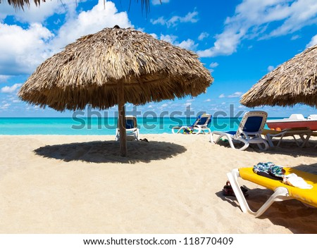 Thatched umbrellas and beach beds on the cuban beach of Varadero - stock photo