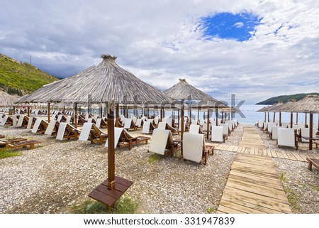 Thatched umbrellas and beach chairs on the beach. Budva, Montenegro