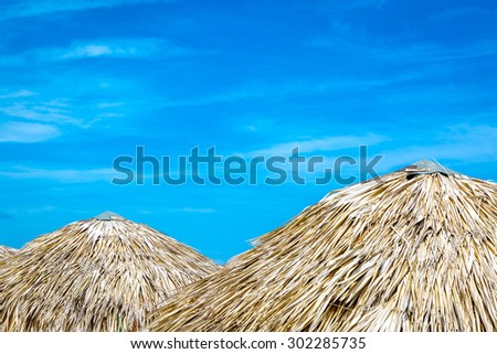 Thatched umbrellas at the famous Varadero beach in Cuba on a beautiful summer day - stock photo