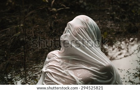 The abduction and Halloween theme: wrapped in a wet cloth person lying in the mud - stock photo