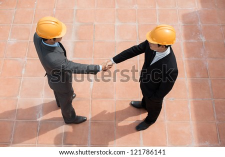 The above-view of businessmen shaking hands on the construction site - stock photo