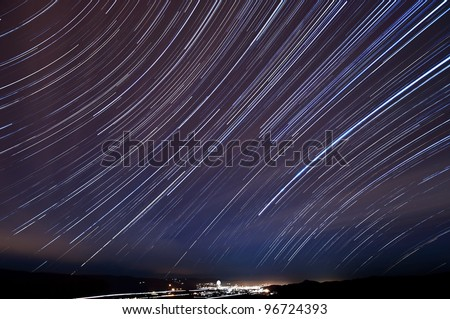 The accumulated star trails in the night sky above Morgan Hill, California. - stock photo