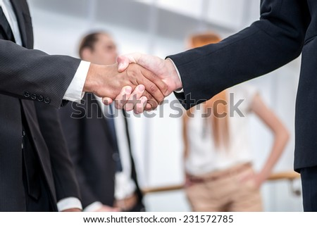 The act of transferring a business. Two Confident businessman firmly shake hands with each other while two colleagues talking in the background - stock photo