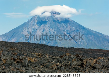 The active lava flow from a new crater on the slopes of volcanoes Tolbachik, on background volcano Bolshaya Udina - Kamchatka, Russia - stock photo