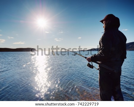 The active man is fishing on sea from the rocky coast. Fisherman check pushing bait on the fishing line, prepare rod and than throw lure into cold water. Fisherman silhouette at sunset