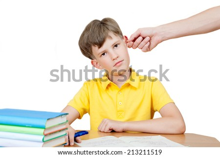 the adult hand holding the ear of the schoolchild - stock photo