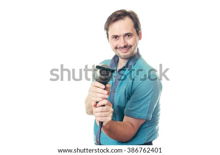 The adult man with a beard in a blue shirt holds the hair dryer in hand and smiles. - stock photo