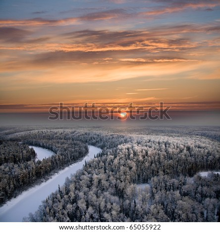 The Aerial view of snow-covered forest in time of sunny winter evening. - stock photo