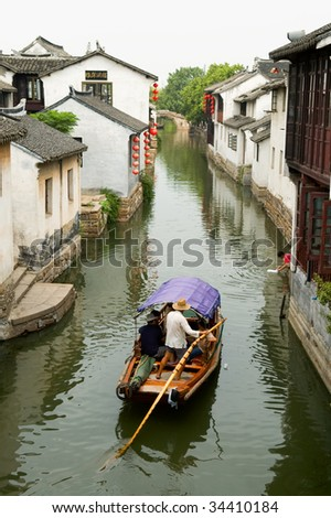 The aerial view of water town in China, with boat man rowing on river - stock photo