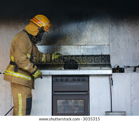 The aftermath of a kitchen oil fire. A firefighter investigating the cause. - stock photo
