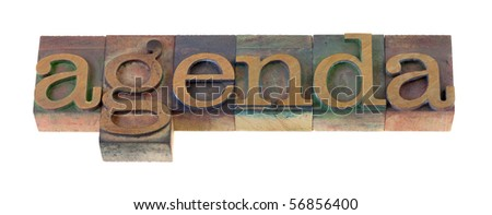 the  agenda word  in vintage wooden letterpress type blocks, stained by color ink, isolated on white