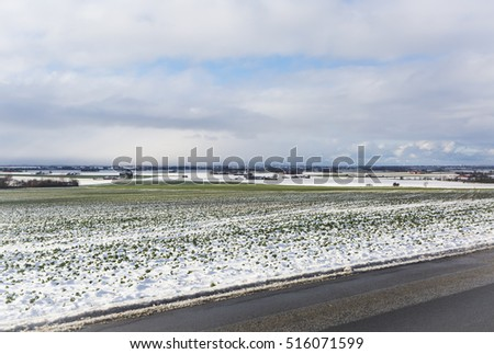 The agriculture landscape of Skane, Sweden, when the first snow has arrived and a white outfit covers the landscape