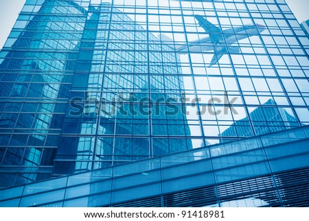 the aircraft reflected in the modern glass building