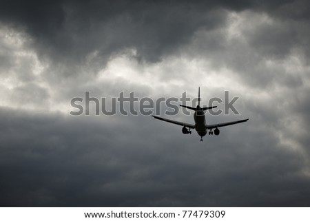 The airplane is landing in the bad weather - stock photo
