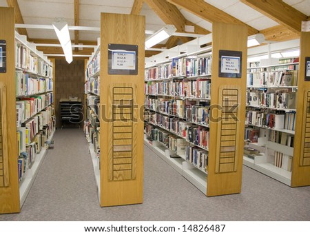 The aisles in a public library with shelves full of books. - stock photo