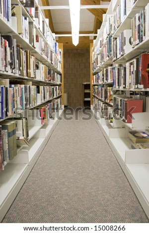 The aisles in a public library with shelves full of books. Any legible book titles or cover artwork have been blurred for copyright reasons.