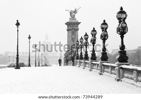 The Alexandre III bridge of Paris under the snow with the Invalides in the background - stock photo