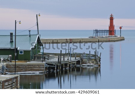 The Algoma Pierhead Light guards the Algoma Harbor at twilight, while the Ahnapee River flows past docks and harbor buildings as it enters Lake Michigan, Kewaunee County, Wisconsin - stock photo
