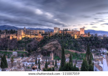 the alhambra palace at twilight, in granada (spain), with sierra nevada mountains in the background - stock photo