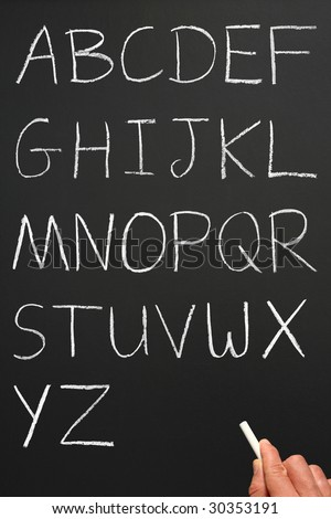 The alphabet in capitals written with white chalk on a blackboard. - stock photo