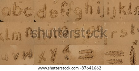 The alphabet written in sand on a beach. - stock photo