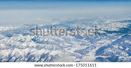 The Alps in winter out of the plane, Aerial Panorama - stock photo
