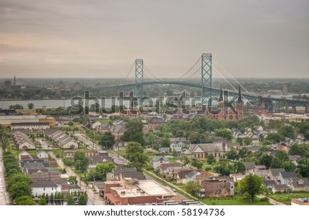 The Ambassador Bridge that spans both Canada and the United States. Taken on an overcast, summer day. Southwest Detroit can be seen in the foreground and Windsor, Canada across the river.