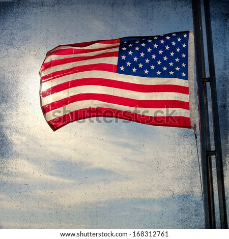 The American Flag Flapping Against A Blue Sky On A Flag Pole. Vintage background