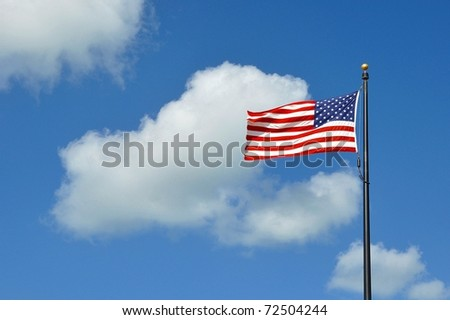 The American Flag Flying Against A Blue Sky With White Clouds On A Windy Day - stock photo