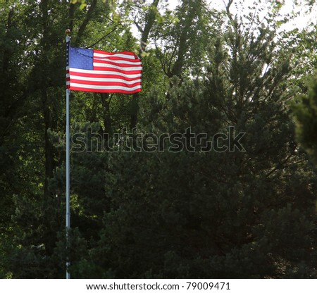 The American flag illuminated against the setting sun - stock photo
