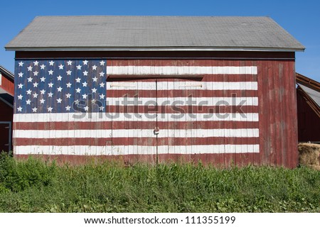The American flag is painted on the front of an old barn. - stock photo