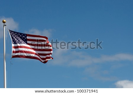 The American flag wavering against a blue  sky - stock photo