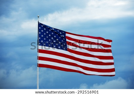 The American flag waves against a cloudy blue sky