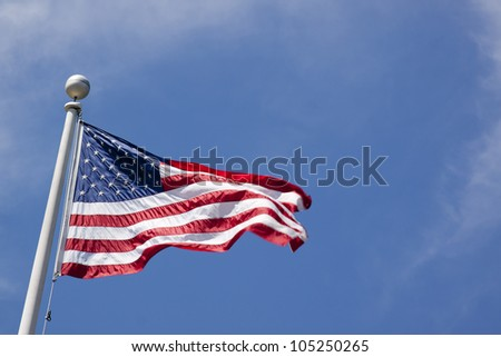 The American flag waving against a blue sky background