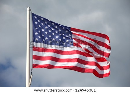 The American flag waving against a cloudy sky