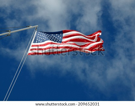 The American Flag Waving Before Wispy Clouds and a Blue Sky - stock photo