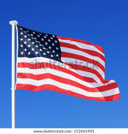 The American flag waving in blue sky - stock photo