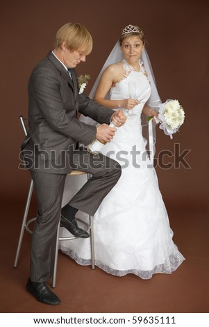 The amusing bride scaredly waits for a popping champagne - stock photo