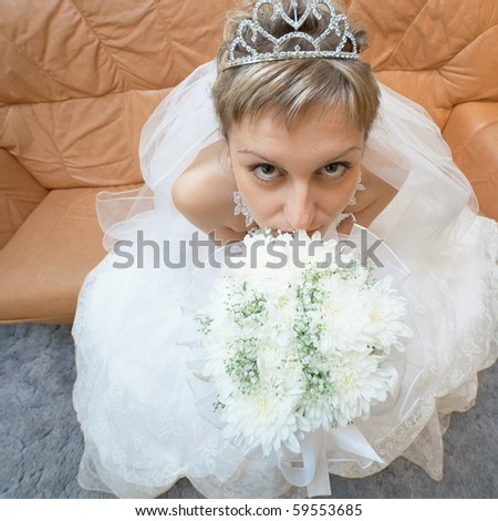 The amusing bride sits on a sofa with a bouquet - the top view - stock photo