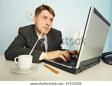 The amusing businessman drinks coffee through a straw without distracting from work in the Internet - stock photo