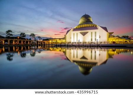 The An-Nur Mosque, Tronoh, Perak during sunrise in reflection on the water. Public Muslim Mosque. (Visible noise due to high ISO, soft focus) - stock photo