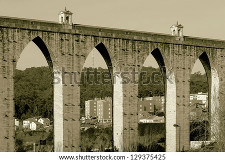 The ancient aqueduct in the Lisbon built in 18th century, Portugal (stylized retro) - stock photo