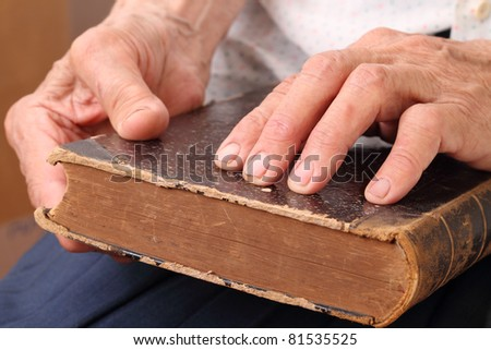The ancient book in hands at the blind old woman