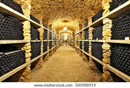 The ancient bottles of wine in the ancient cellar. The unique vintage wine in the cellar.Old bottles of wine in rows in wine cellar.. - stock photo
