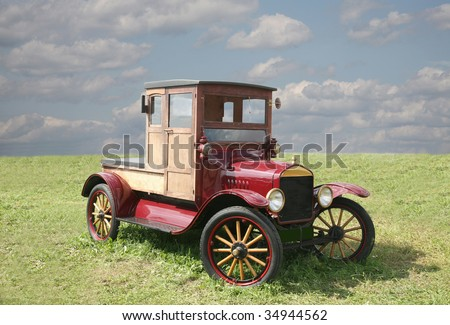 The ancient car  of red color with wooden wheels - stock photo