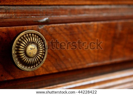 The ancient decorative handle of a box of a wooden desk. - stock photo