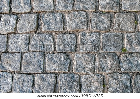 The ancient paving blocks of marble. Texture of antique marble. The ancient cobbled street. Paving stones of historic European streets. The texture and the background paving. - stock photo