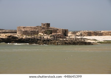 The ancient ruins of Castelo Real of Mogador sitting in the water off the fishing port of Essaouira, Morocco.